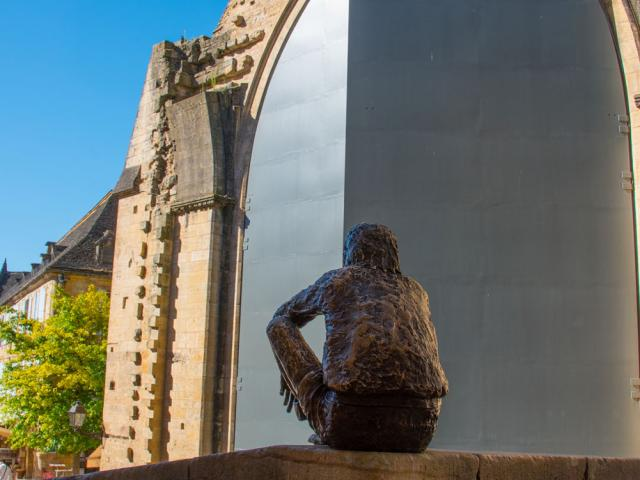 Statue du Badaud à Sarlat devant les portes de l'ancienne église Sainte-Marie